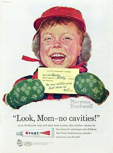 Squinty open smile on a boy wearing a red winter hat and green mittens and holding a yellow exam note says 'Look Mom no cavities' in another Crest toothpaste ad print by Norman Rockwell.
