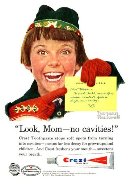 Norman Rockwell painting of a girl in a brown bob and green cap points to a yellow note about her dental checkup and yells 'Look, Mom - no cavities!' Ad copy: Crest Toothpaste stops soft spots from turning into cavities - means far less decay for grownups and children. And Crest freshens your mouth - sweetens your breath.