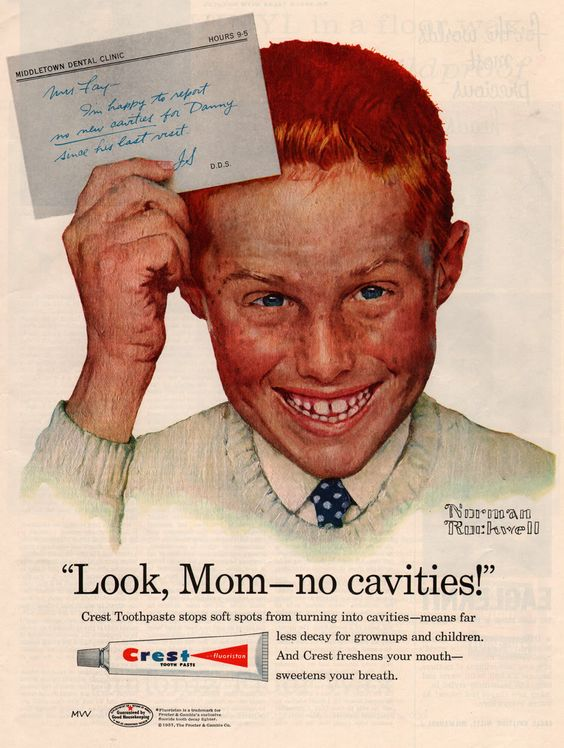 Redhead freckled boy in a buzz cut and tie holds a note above his head to Mrs. Faye, I'm happy to report no new cavities for Danny since his last visit, J.S. D.D.S. A Norman Rockwell portrait for Crest's first fluoride toothpaste in the 1950s.