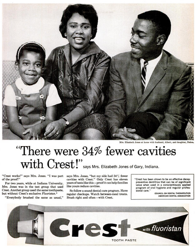 African-American parents and daughter sitting on their couch. Mother is quoted, 'There were 34% fewer cavities with Crest!' says Mrs. Elizabeth Jones of Gary, Indiana.  Additional copy and image of Crest toothpaste in box below.