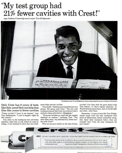 Black and white magazine ad for Crest from the 1960s shows young African-American man in suit and tie at a music stand, identified as Toothpaste tester Tom Bridgewater majoring in music at Indiana University, and saying 'My test group had 21% fewer cavities with Crest!' Copy below includes headline 'Only Crest has 9 years of tests like this - proof that can help families like yours to fewer cavities.' Box of Crest toothpaste at bottom of ad shows the ADA statement about Crest on the side of the box.