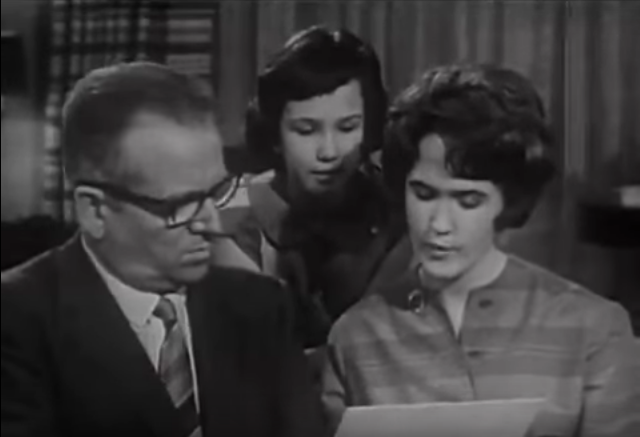 Screenshot from a 1960s television ad for Crest featuring an interviewer TV dude interviewing a White family about how Crest did for their teen daughter's participation in the tests. Teen daughter shows results on a handout to the interviewer guy while younger sister looks on over her shoulder.