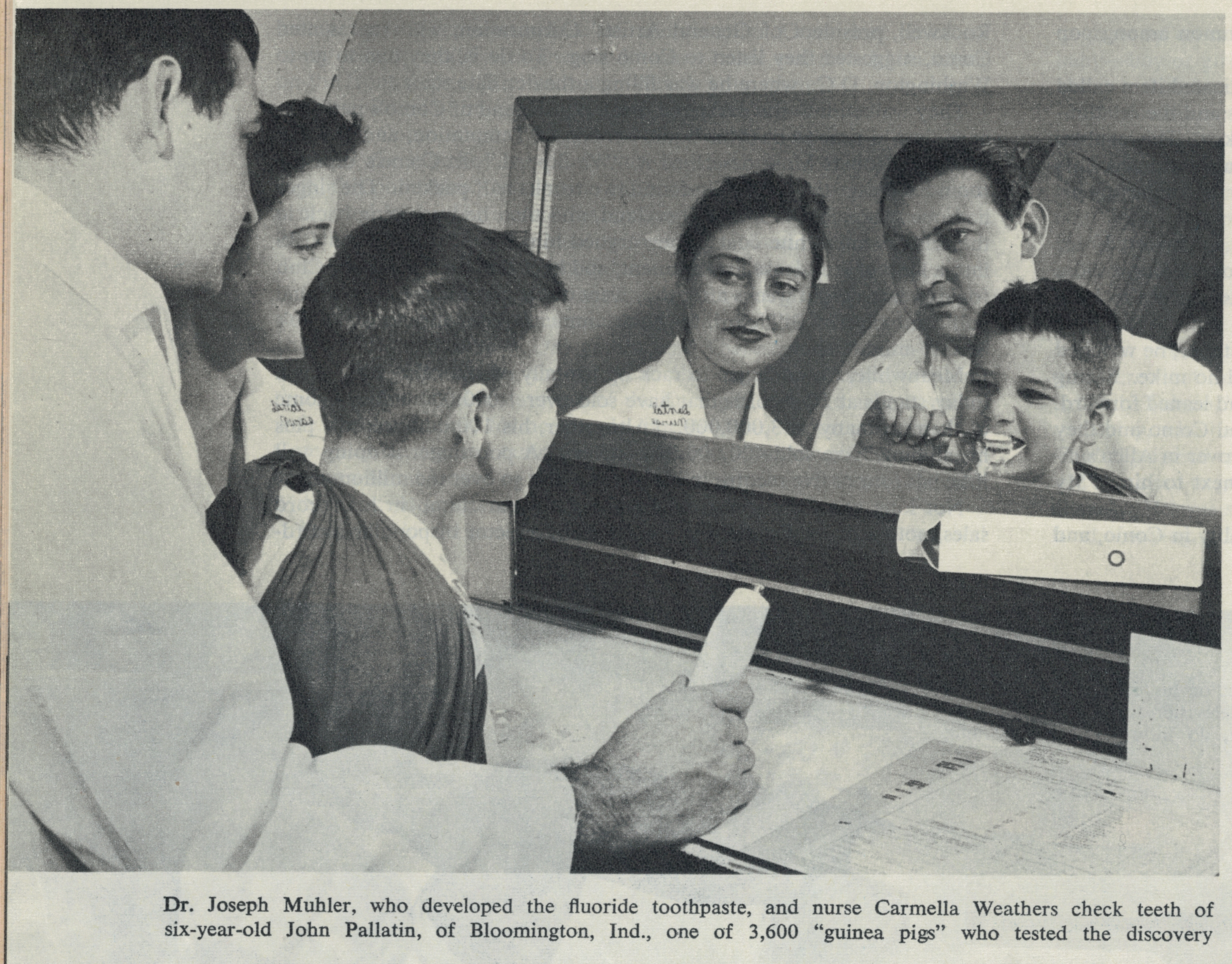 Black and white magazine photo of a nurse, a dentist, and a kid looking in a mirror as the child brushes his teeth.