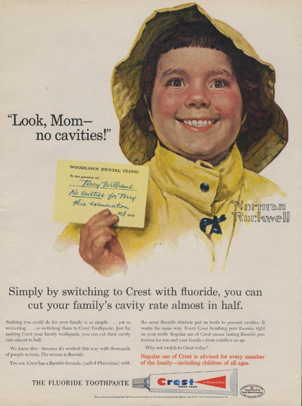 Mid-century magazine ad for Crest's stannous fluoride in toothpaste shows Norman Rockwell's drawing of little kid Terry Williams in a yellow rain hat and jacket, saying the slogan 'Look Mom no cavities,' and holding up a note from Woodlawn Dental Clinic saying 'To the proud parents of Terry Williams No cavities for Terry this examination.' Readable ad copy below: Simply by switching to Crest with fluoride, you can cut your family's cavity rate almost in half. Regular use of Crest is advised for every member of the family - including children of all ages. The fluoride toothpaste, plus a drawing of a tuble of Crest toothpaste.