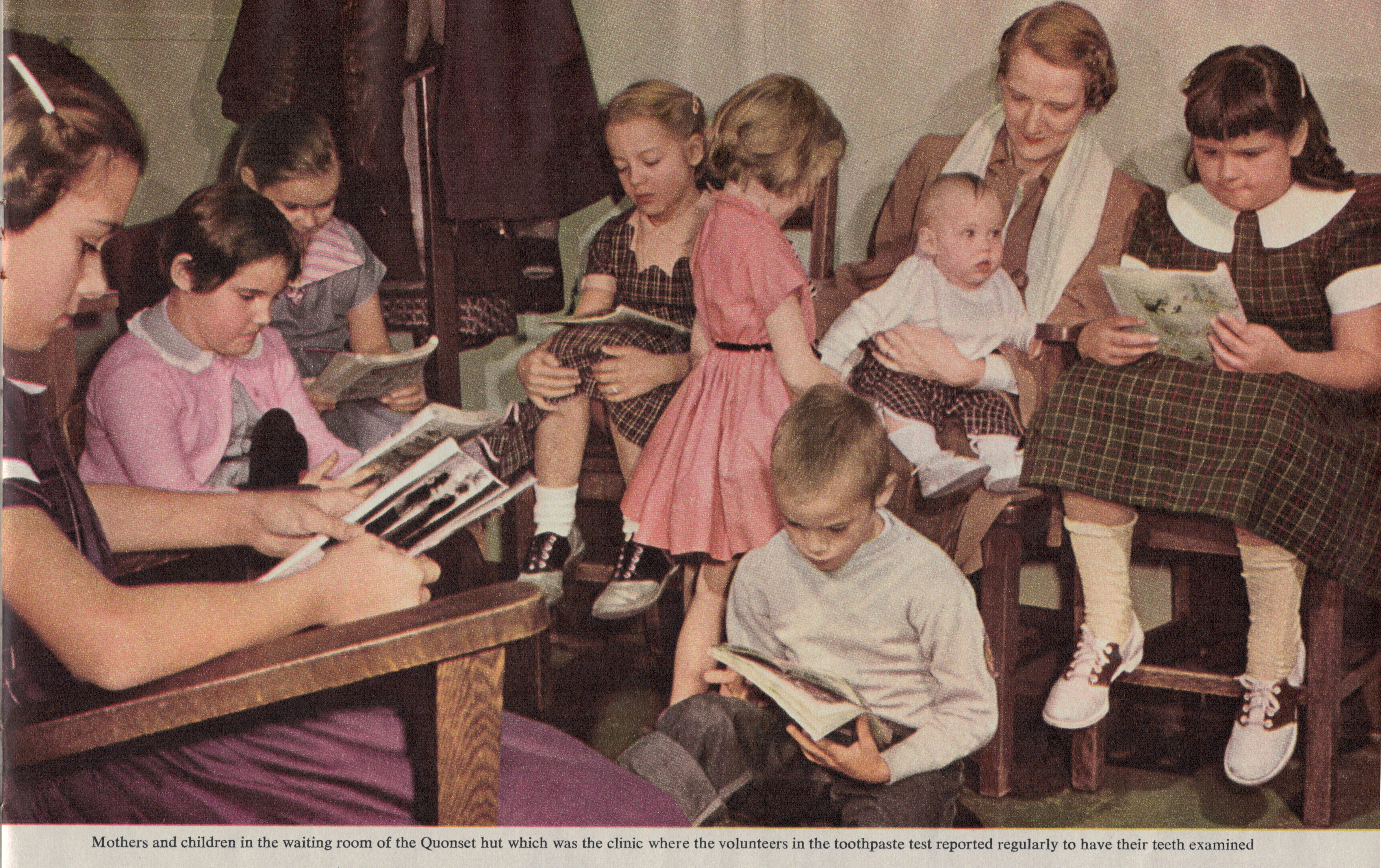 Color photograph from a 1950s magazine shows kids and parents waiting in a clinic. Five girls in clothes such as pink sweaters, Oxford shoes and checkered dresses sit in wooden chairs and read comic books and magazines. One boy on the floor reads a magazine. One girl in pink plays with a baby sitting on a mother's lap.