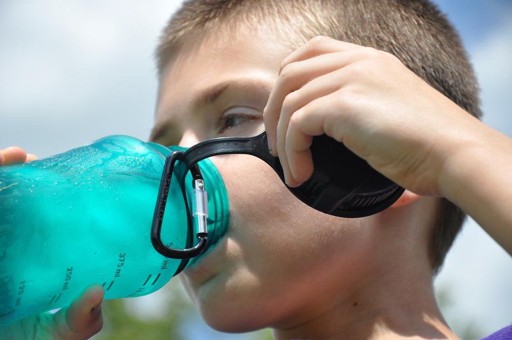 Boy drinks fluoridated water from bottle