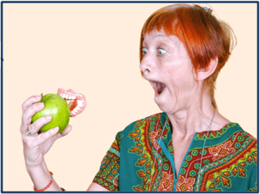 Cheeky redhead woman looking at her dentures popped out stuck in an apple she was biting into