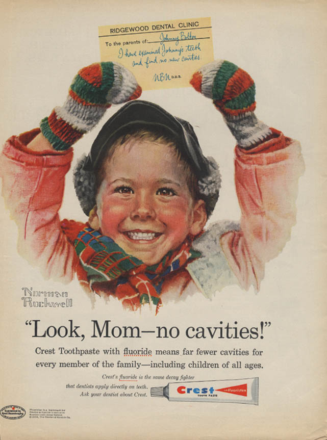 Kid in red coat, knitted mittens, and warm winter cap and scarf, holds a note from Ridgewood Dental Clinic over his head. Slogan and writing below say Look, Mom - no cavities! Crest Toothpaste with fluoride means far fewer cavities for every member of the family - including children of all ages. Crest's fluoride is the same decay fighter that dentists apply directly on teeth. Ask your dentist about Crest.