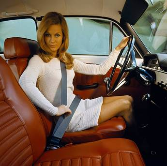 Historic Volvo ad promoting seat belts - woman looks at camera while buckling her 3-point seat belt